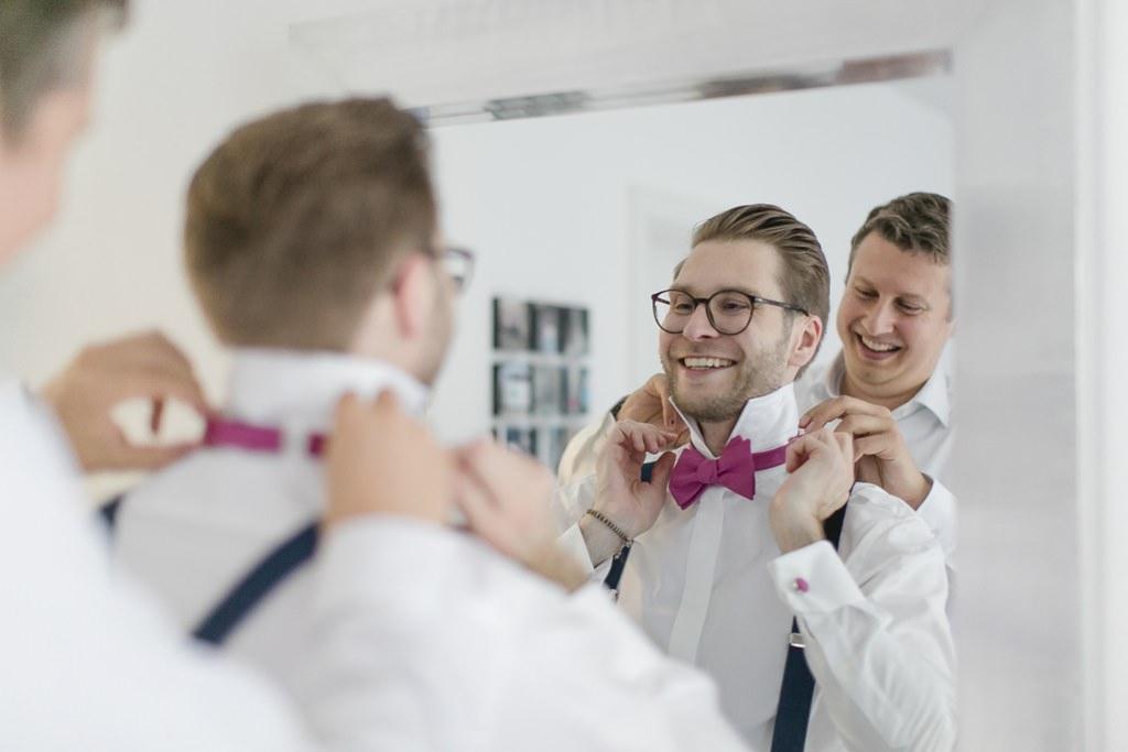 der Trauzeuge hilft dem Bräutigam beim Anlegen der pinkfarbenen Fliege | Foto: Hanna Witte