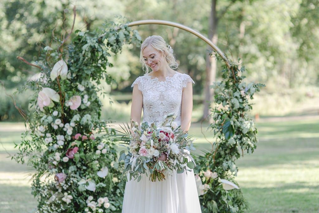 Hochzeitsfoto von der Braut mit ihrem Brautstrauß vor einem Greenery Hochzeitsbogen | Foto: Hanna Witte