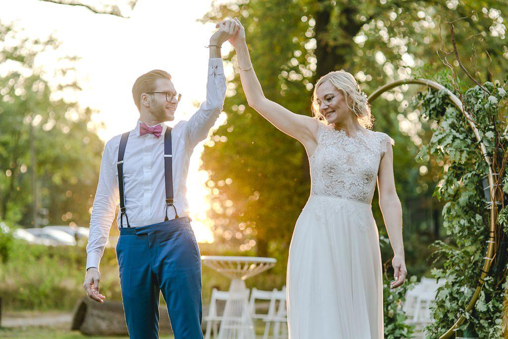 Outdoor Hochzeitsfoto mit Sonnenuntergang: Braut und Bräutigam halten sich an den Händen | Foto: Hanna Witte