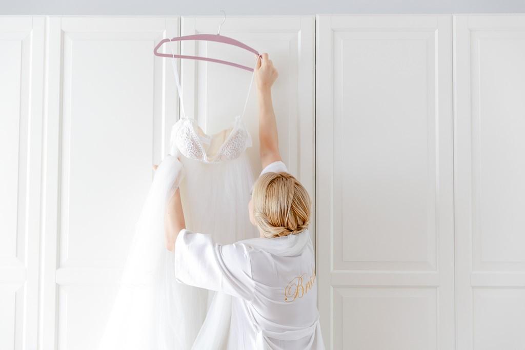 die Braut nimmt beim Getting Ready ihr Brautkleid vom Kleiderbügel | Foto: Hanna Witte