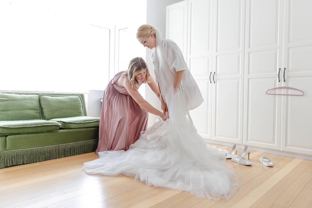 die Trauzeugin hilft der Braut beim Anziehen des Brautkleids | Foto: Hanna Witte