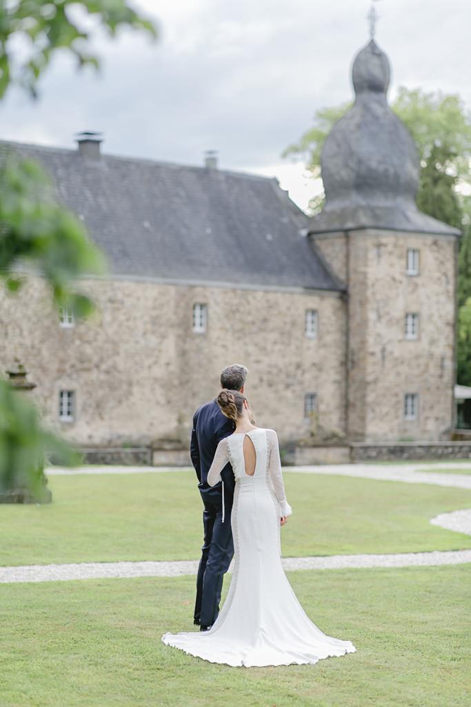 das Brautpaar steht Arm in Arm vor Schloss Ehreshoven | Foto: Hanna Witte