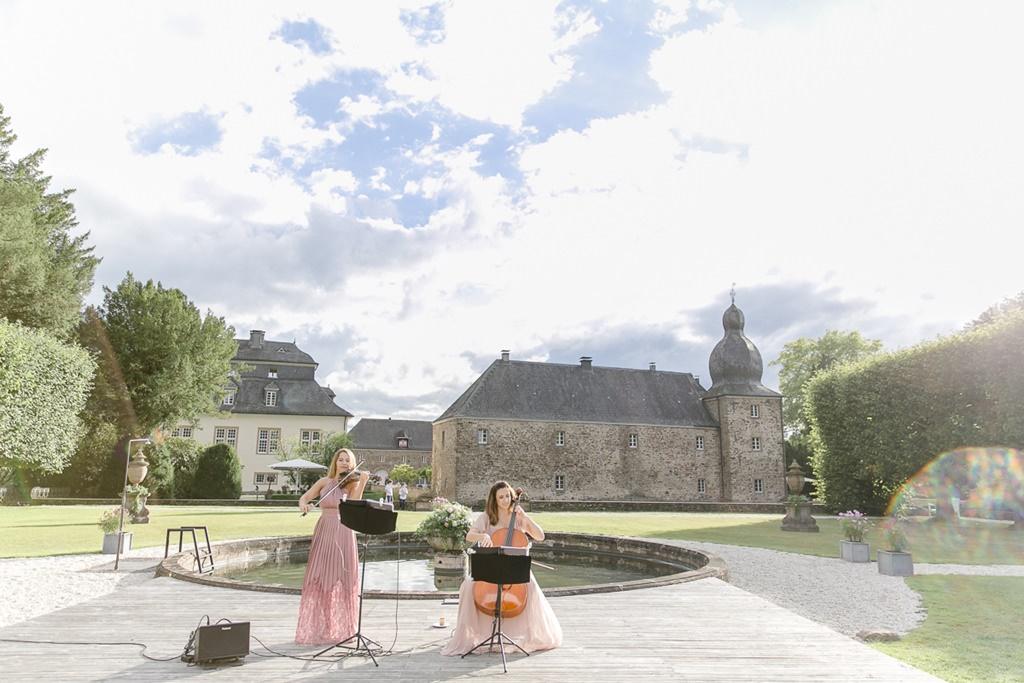 Hochzeitsmusikerinnen mit Geige und Cello spielen vor einem Brunnen von Schloss Ehreshoven | Foto: Hanna Witte