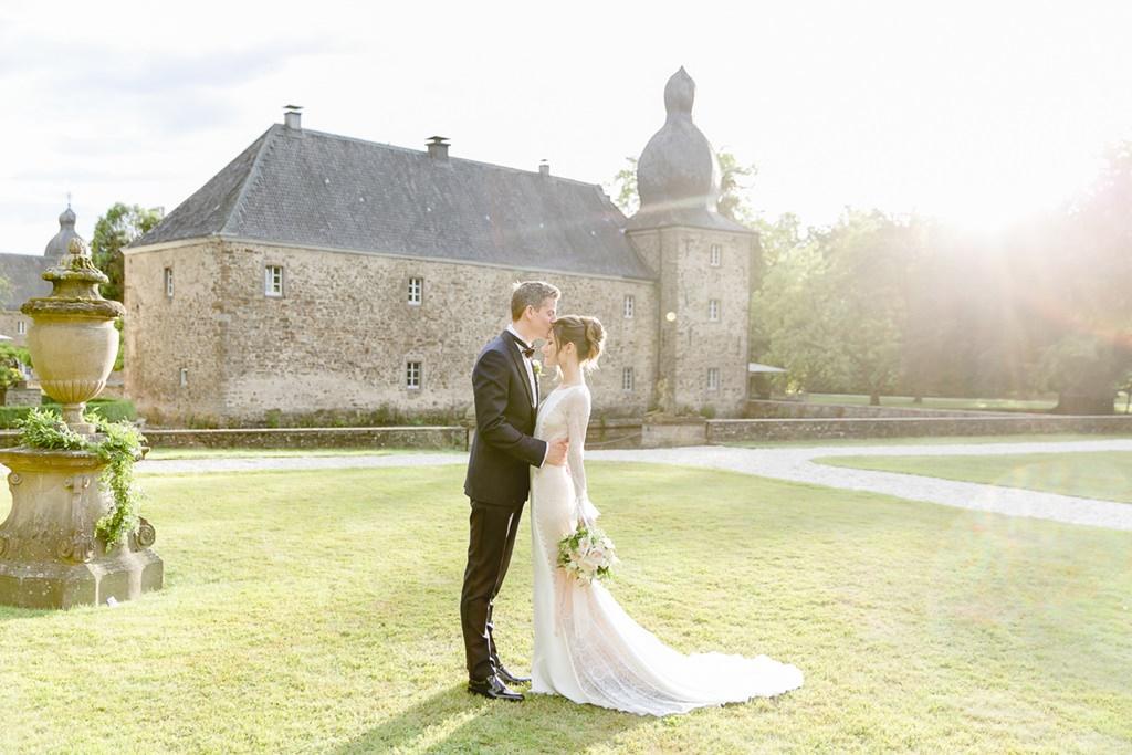 das Brautpaar küsst sich auf einer Wiese vor Schloss Ehreshoven | Foto: Hanna Witte