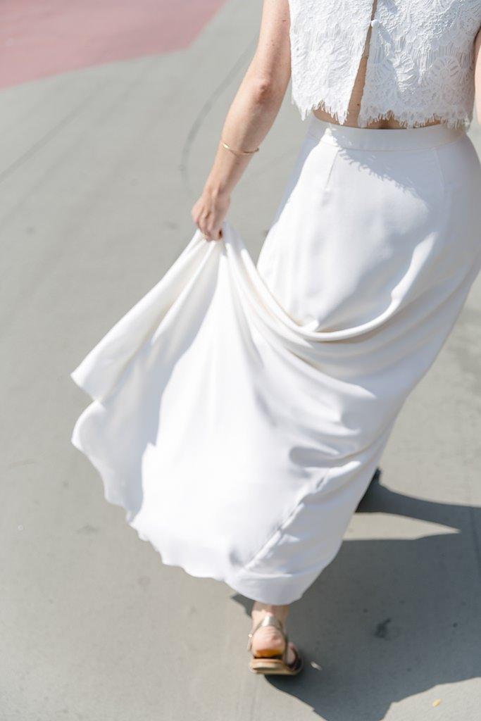 Brautkleid mit langem, schlichten Rock und Spitzenoberteil | Foto: Hanna Witte