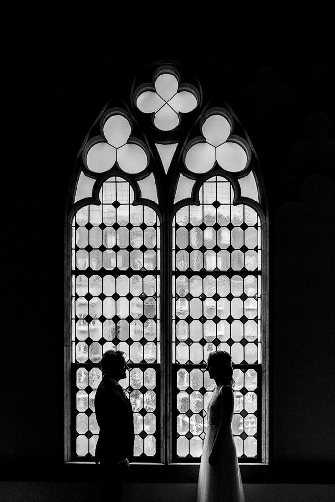 schwarz-weiß Paarfoto vor einem hohen Kirchenfenster | Foto: Hanna Witte
