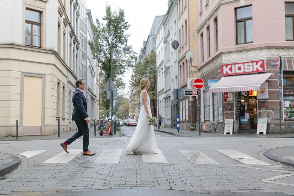 urbanes Paarfoto von Braut und Bräutigam, die über einen Zebrastreifen laufen | Foto: Hanna Witte
