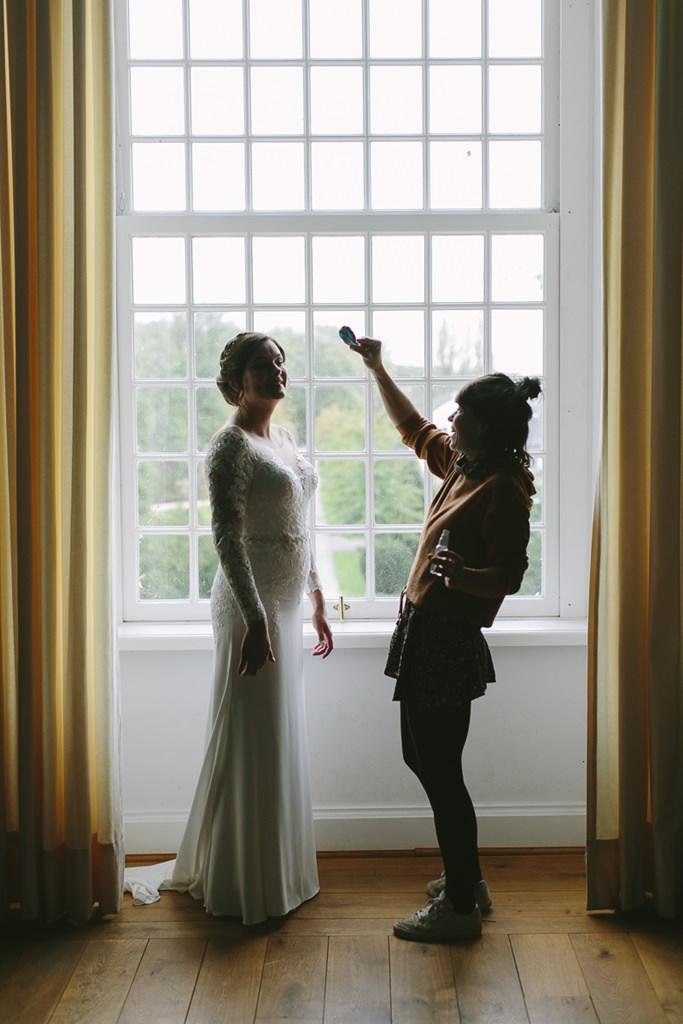 die Braut wird vor einem großen Fenster für die Hochzeit gestylt | Foto: Hanna Witte