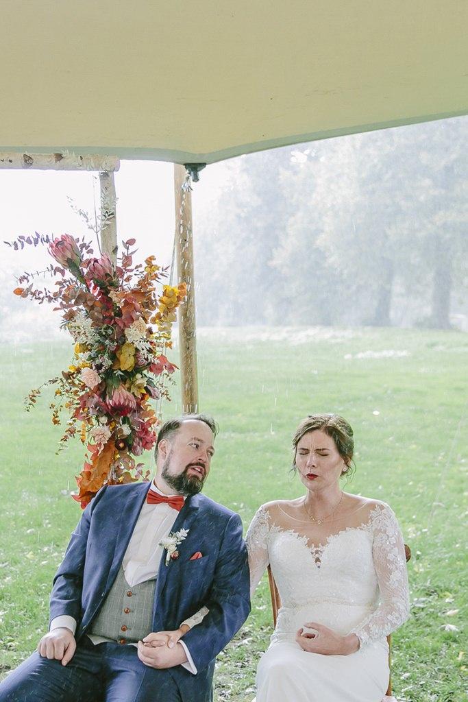die Braut kneift während der Trauung die Augen zu, da der Regen einsetzt | Foto: Hanna Witte