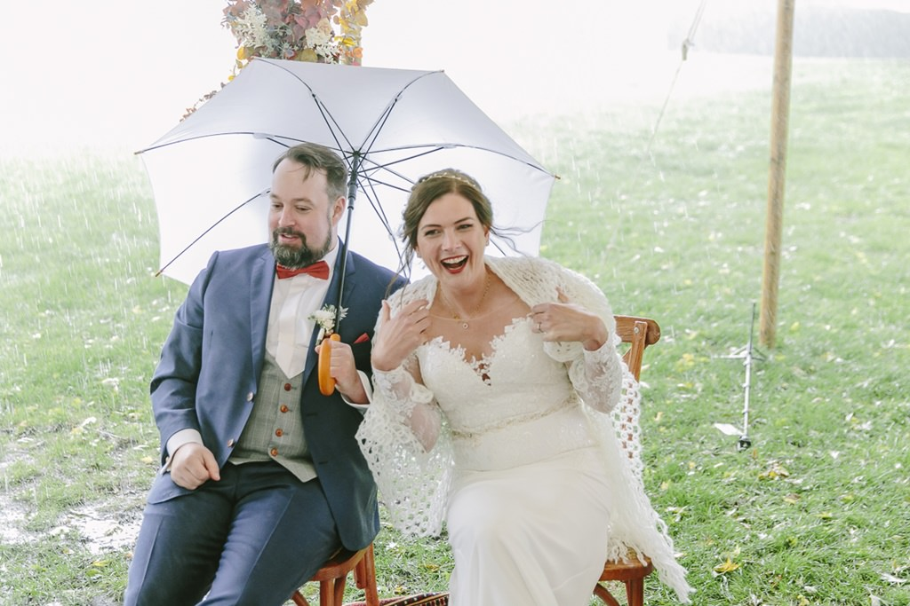 Hochzeitsfoto bei Regen: Die Braut lacht, während es bei der Trauung im Freien regnet die Braut sitzt an einem Tresen im stylischen 25hours Hotel The Circle in Köln | Foto: Hanna Witte