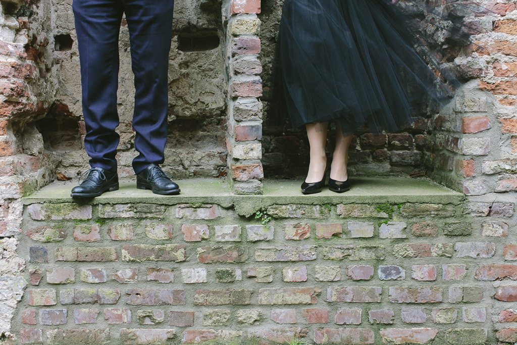 Paarfotoidee: Das Brautpaar steht in einer alten Ruine und man sieht nur Füße und Beine | Foto: Hanna Witte