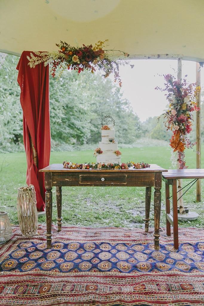 Semi Naked Cake Hochzeitstorte mit bunten Blumen, die auf einem Vintage Tisch steht | Foto: Hanna Witte