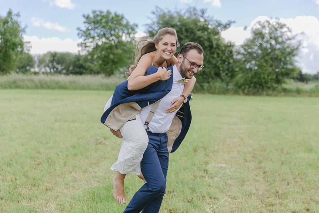 ungestelltes Hochzeitsmotiv: Der Bräutigam trägt die Braut auf dem Rücken | Foto: Hanna Witte