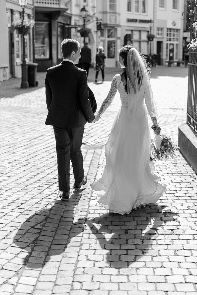 Hochzeitsmotiv in schwarz-weiß: Das Brautpaar läuft Hand in Hand durch die Stadt | Foto: Hanna Witte