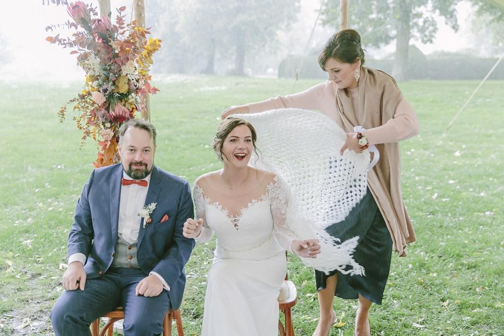spontanes Hochzeitsmotiv: Während der Trauung im Freien setzt Regen ein und die Braut zieht sich eine Stola über | Foto: Hanna Witte