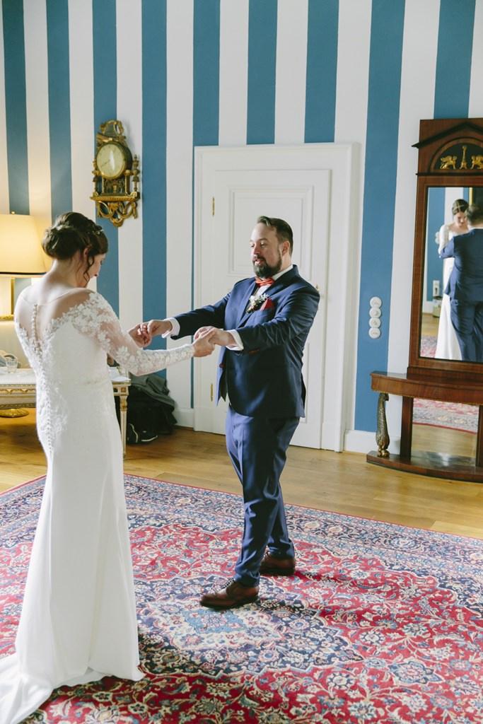 Hochzeitsmotiv First Look: Der Bräutigam bewundert seine Braut und ihr Brautkleid | Foto: Hanna Witte