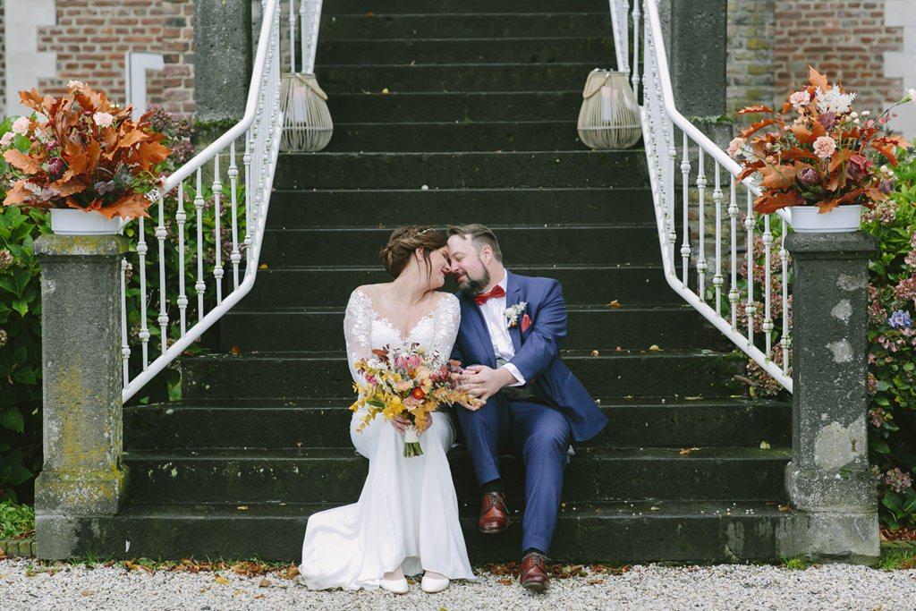das Brautpaar sitzt für das Hochzeitsfoto auf einer Treppe | Foto: Hanna Witte