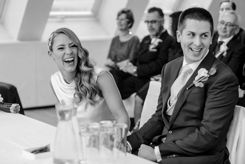 ungestelltes Hochzeitsmotiv: Das Brautpaar lacht während der Trauung | Foto: Hanna Witte