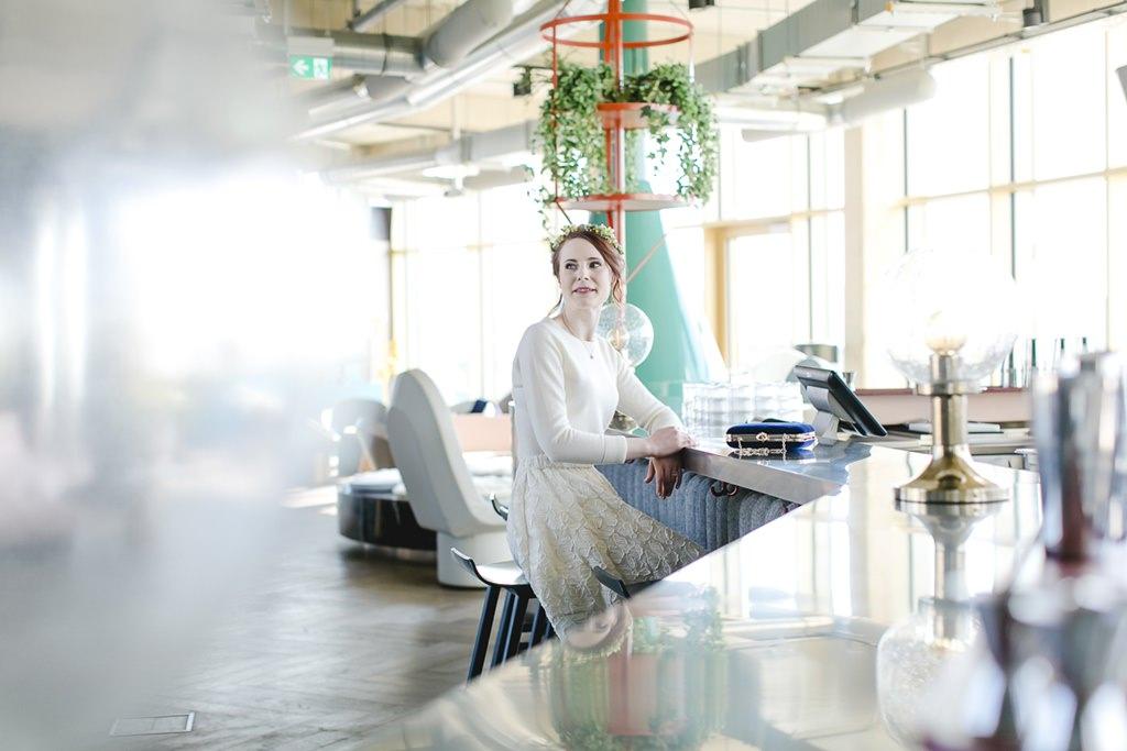 die Braut sitzt an einem Tresen im stylischen 25hours Hotel The Circle in Köln | Foto: Hanna Witte