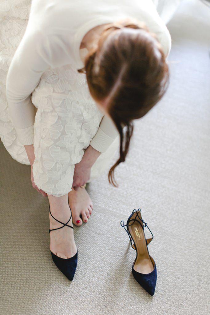 die Braut zieht sich beim Getting Ready ihre dunkelblauen Brautschuhe an | Foto: Hanna Witte