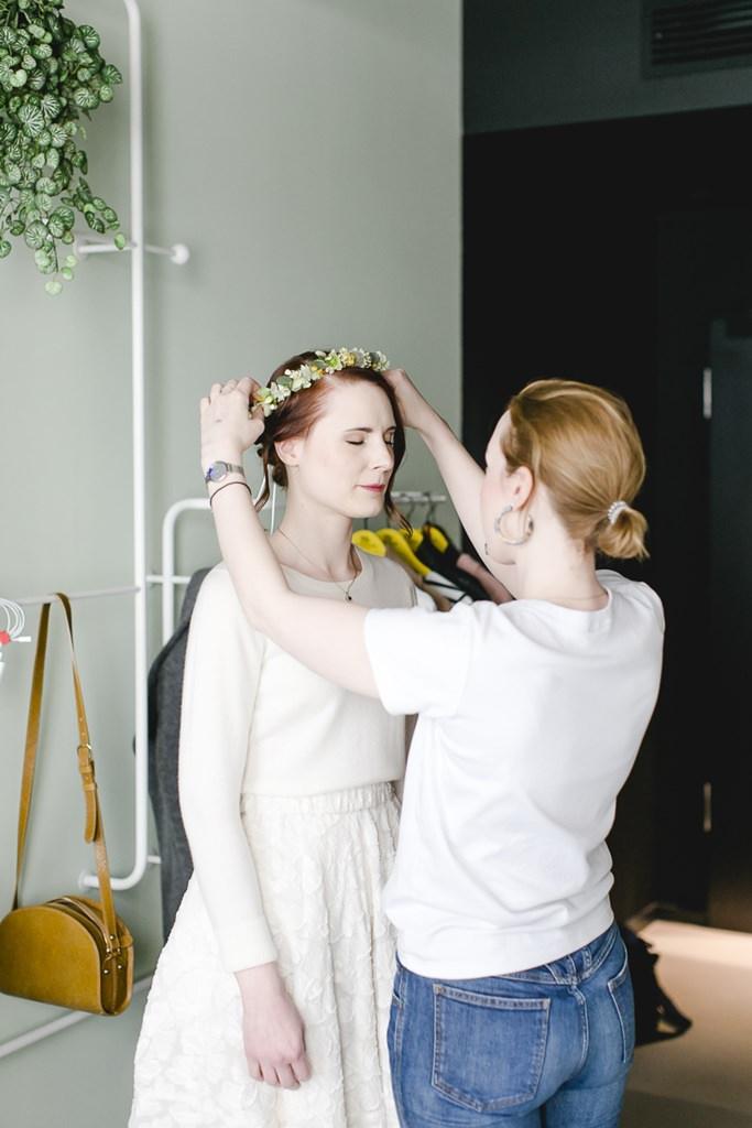 die Stylistin richtet beim Getting Ready den Blumenkranz im Haar der Braut | Foto: Hanna Witte