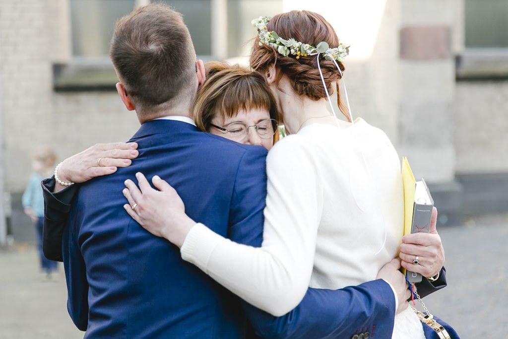 das Brautpaar wird von der Brautmutter umarmt | Foto: Hanna Witte