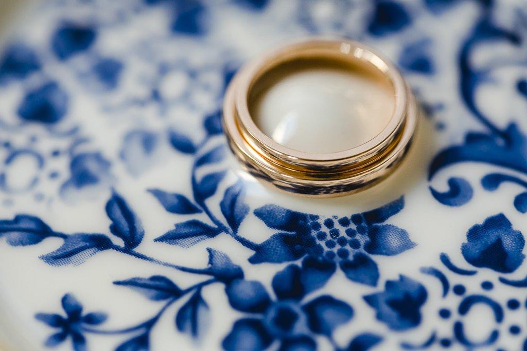 die goldenen Trauringe liegen auf einem blauen Blumenmuster | Foto: Hanna Witte