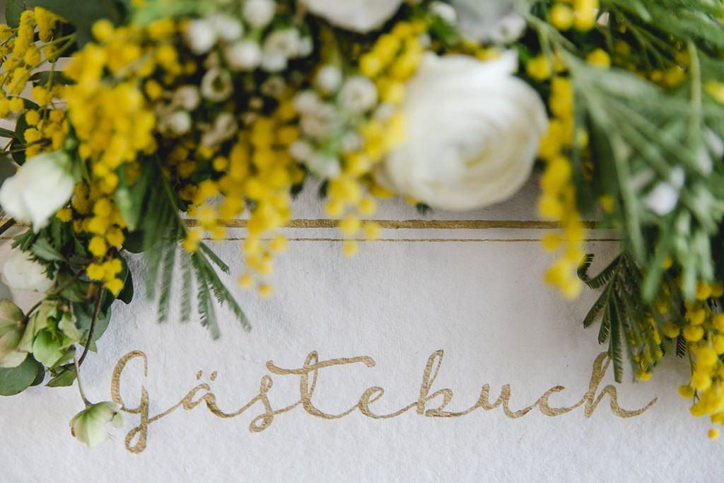 gelbe Mimosen, Greenery und weiße Blumen als Hochzeitsdeko für das Gästebuch | Foto: Hanna Witte