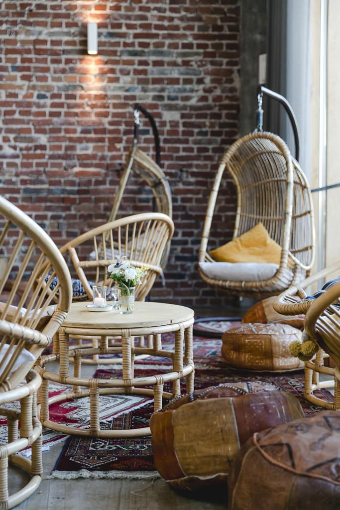 Hochzeitsdeko: Boho Lounge Ecke mit Rattanmöbeln, Leder-Poufs und Teppichen | Foto: Hanna Witte