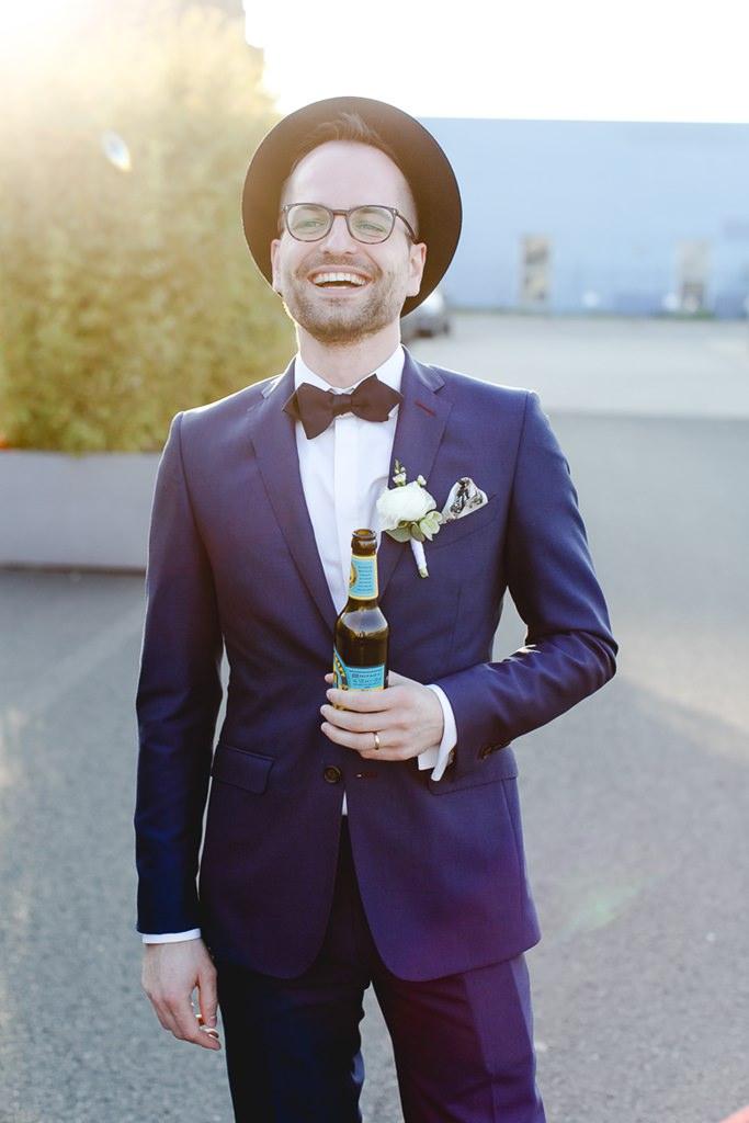 cooles Bräutigamfoto: Der Bräutigam posiert mit lässigem Hut und einer Flasche Bier | Foto: Hanna Witte