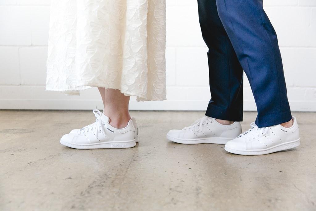 Braut und Bräutigam tragen beide weiße Adidas Sneaker | Foto: Hanna Witte Hochzeitsreportagen