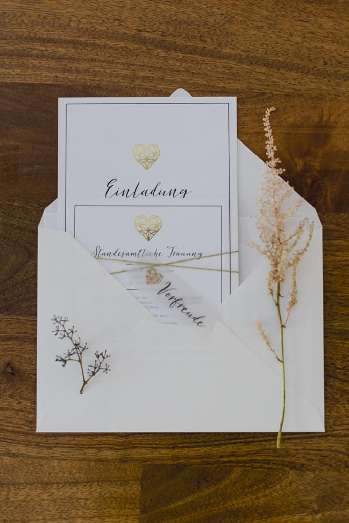 schlichte, weiße Hochzeitseinladung mit goldenem Geometrie-Herz | Hochzeitsfoto: Hanna Witte