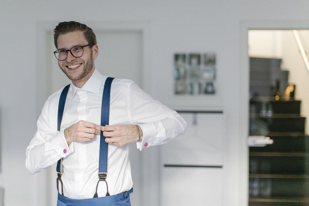 der Bräutigam legt seine blauen Hosenträger an | Hochzeitsfoto: Hanna Witte