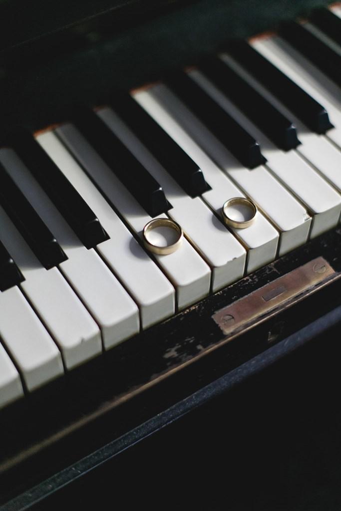 goldene Trauringe auf einer Klaviertastatur | Hochzeitsfoto: Hanna Witte