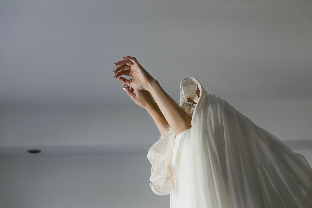 die Braut zieht ihr Brautleid über den Kopf | Hochzeitsfoto: Hanna Witte