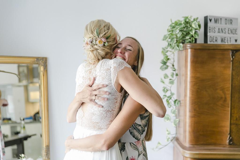 die Braut umarmt beim Getting Ready ihre Trauzeugin | Hochzeitsfoto: Hanna Witte
