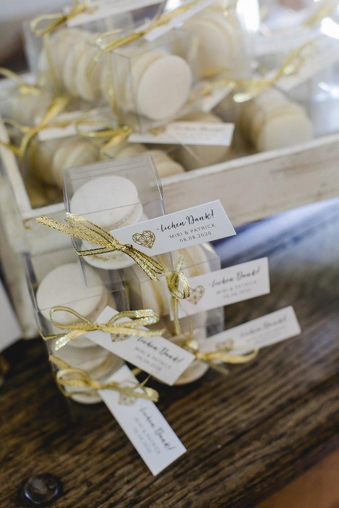 Gastgeschenk Hochzeit: Weiße Macarons mit goldener Schleife | Hochzeitsfoto: Hanna Witte