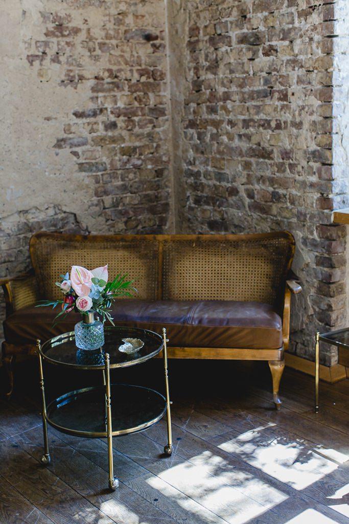 Vintage Couch mit Tisch und Hochzeitsdeko im Rittergut Orr | Hochzeitsfoto: Hanna Witte