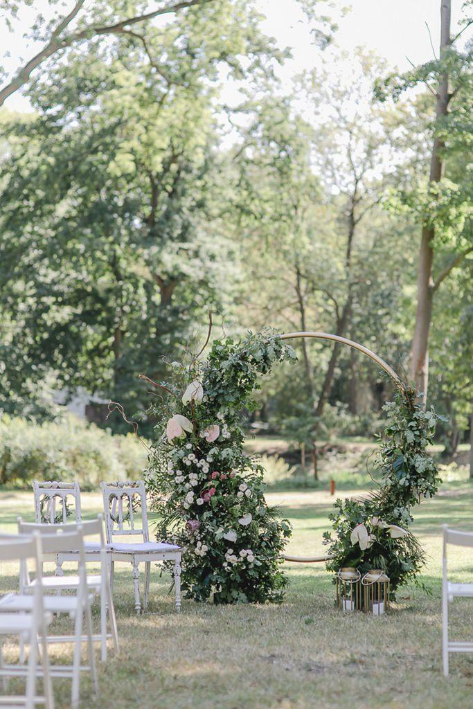 Freie Trauung draußen mit geschmücktem Traubogen und weißen Stühlen | Hochzeitsfoto: Hanna Witte