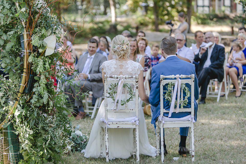 das Brautpaar sitzt auf geschmückten shabby chic Traustühlen | Hochzeitsfoto: Hanna Witte