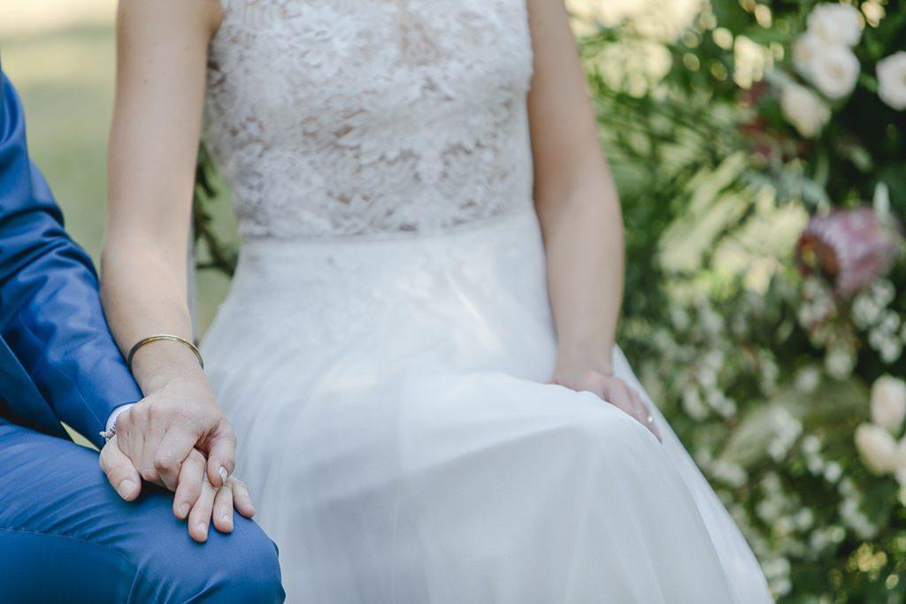 das Brautpaar hält während der Freien Trauung Händchen | Hochzeitsfoto: Hanna Witte