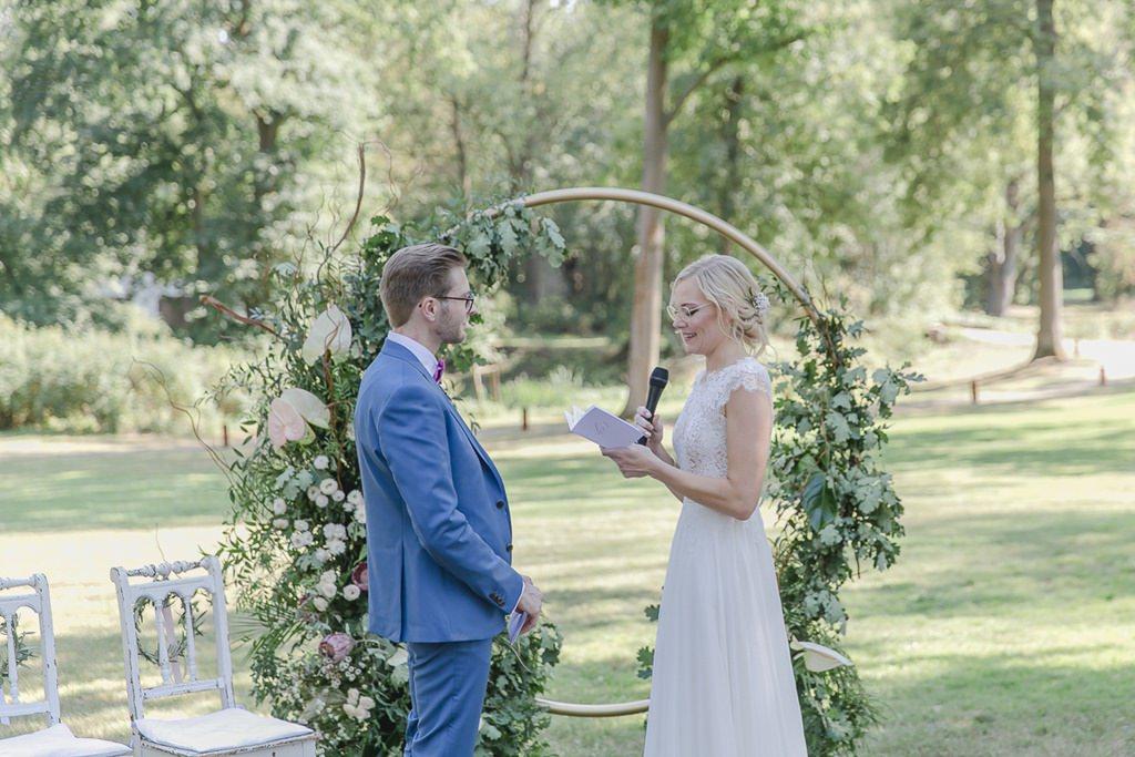 das Brautpaar beim Ehegelübde vor dem Greenery Hochzeitsbogen | Hochzeitsfoto: Hanna Witte