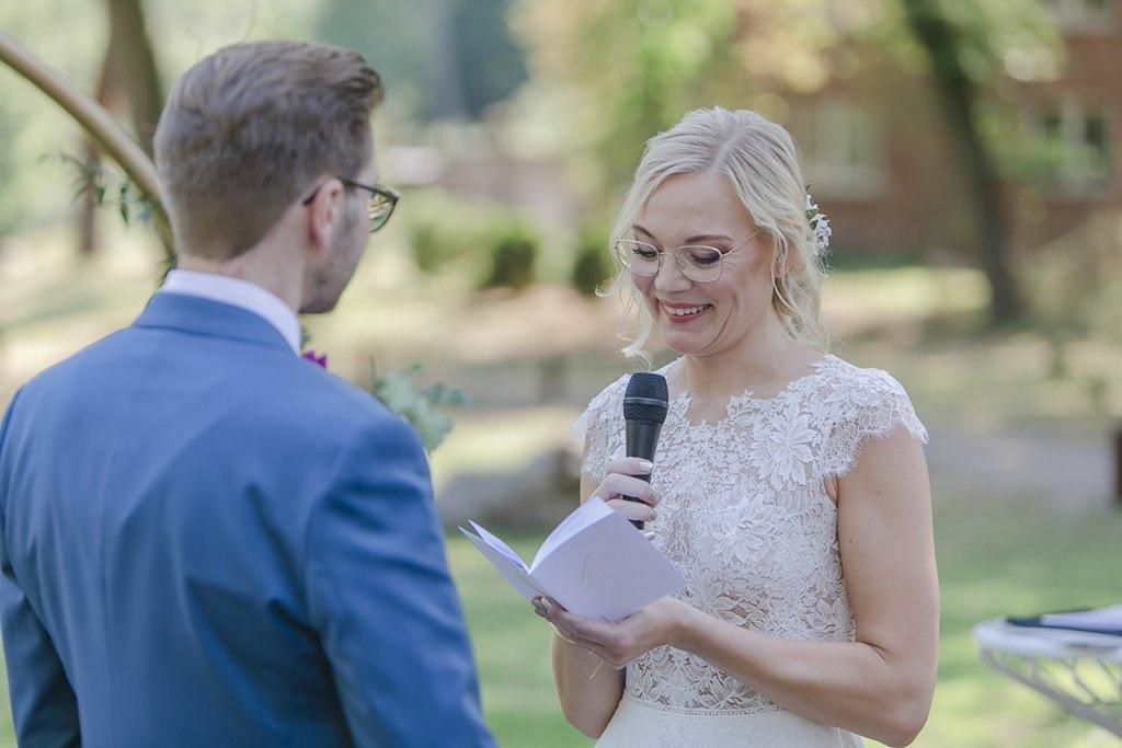 die Braut liest während der Freien Trauung ihr Eheversprechen vor | Hochzeitsfoto: Hanna Witte