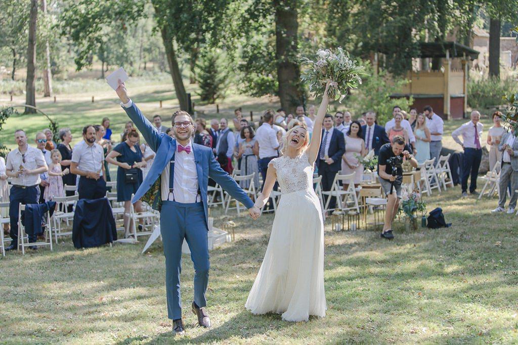 das Brautpaar streckt nach der Freien Trauung jubelnd die Hände in die Höhe | Hochzeitsfoto: Hanna Witte