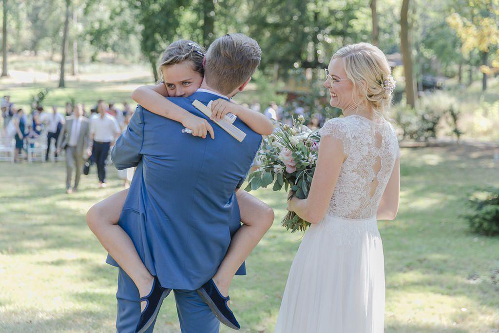 ein kleiner Hochzeitsgast springt dem Bräutigam in die Arme | Hochzeitsfoto: Hanna Witte