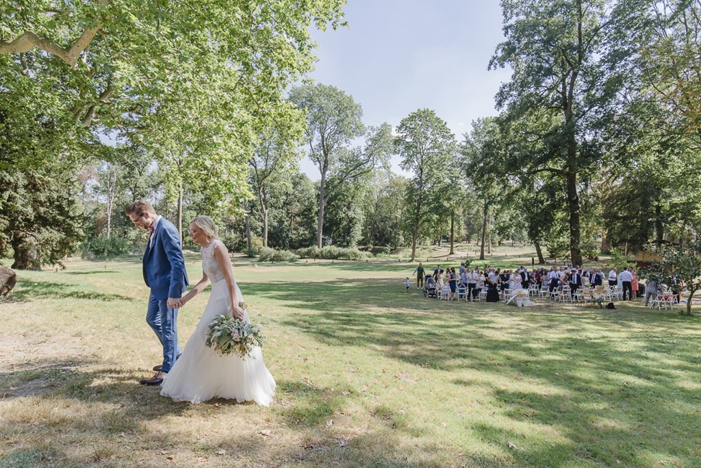 das Brautpaar läuft nach der Trauung Hand in Hand über die Wiese von Rittergut Orr | Hochzeitsfoto: Hanna Witte