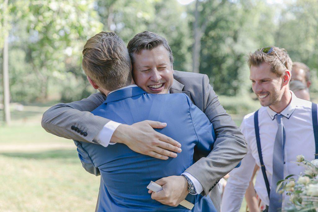 der Bräutigam wird von einem Hochzeitsgast umarmt | Hochzeitsfoto: Hanna Witte
