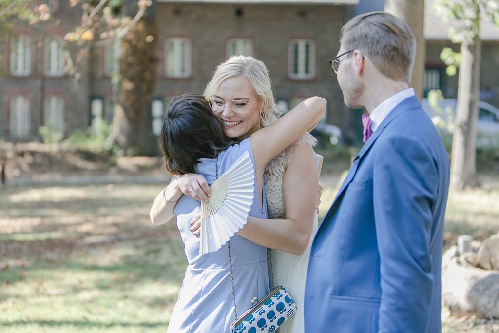 die Braut wird von einem weiblichen Hochzeitsgast umarmt | Hochzeitsfoto: Hanna Witte