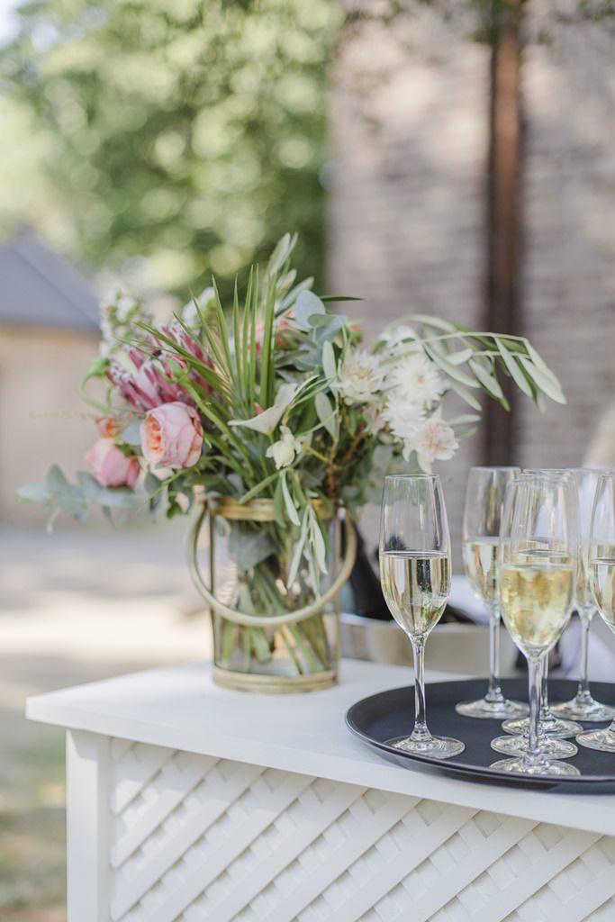 Hochzeitsblumen in einer Henkel-Vase beim Sektempfang | Hochzeitsfoto: Hanna Witte