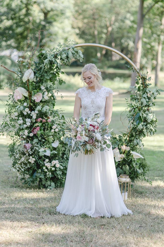 Brautfotoidee: Die Braut steht mit Brautstrauß in der Hand vorm Traubogen | Hochzeitsfoto: Hanna Witte